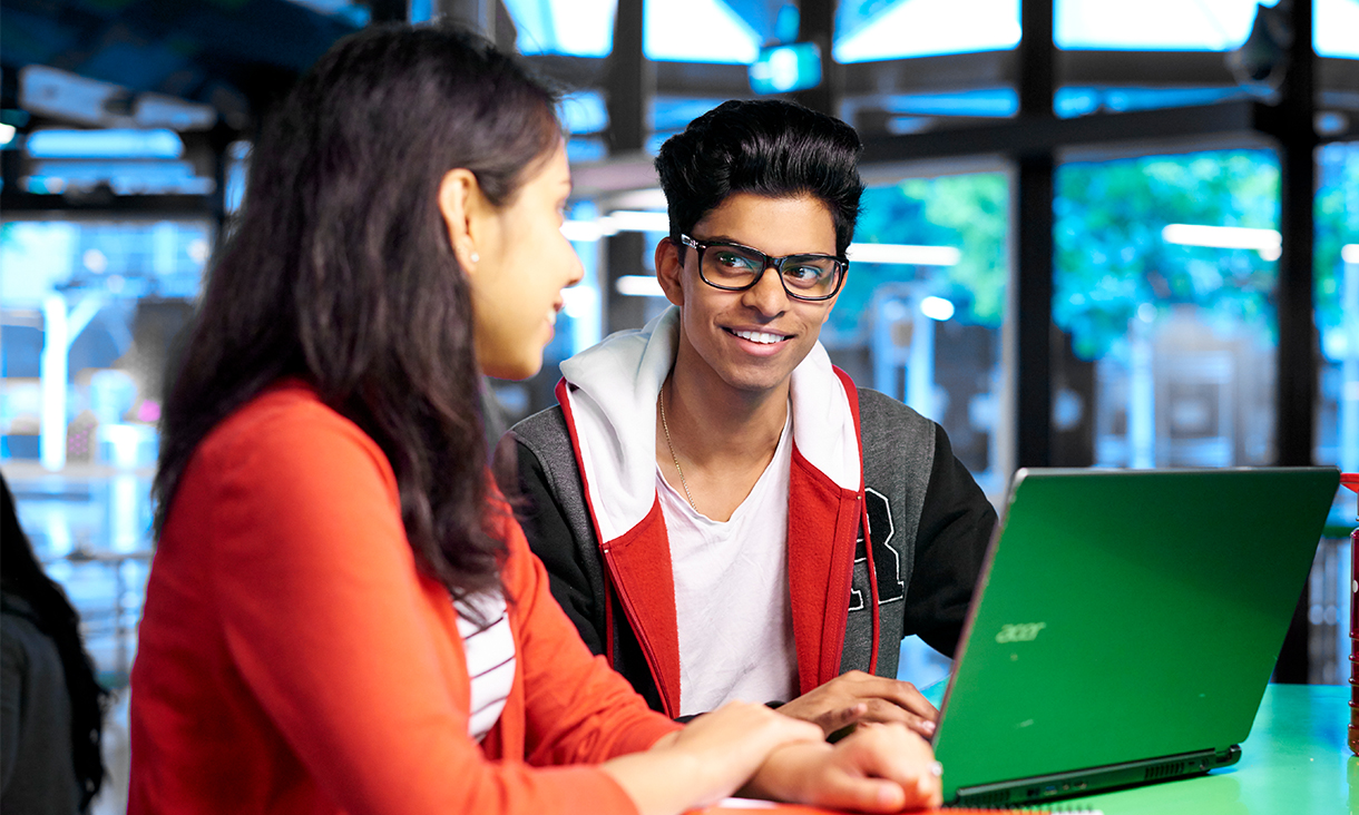 Two student sharing a laptop